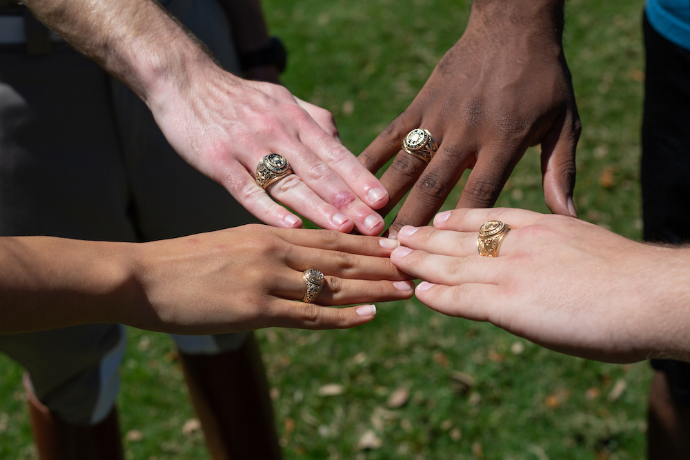 hands in the circle showing Aggie Rings