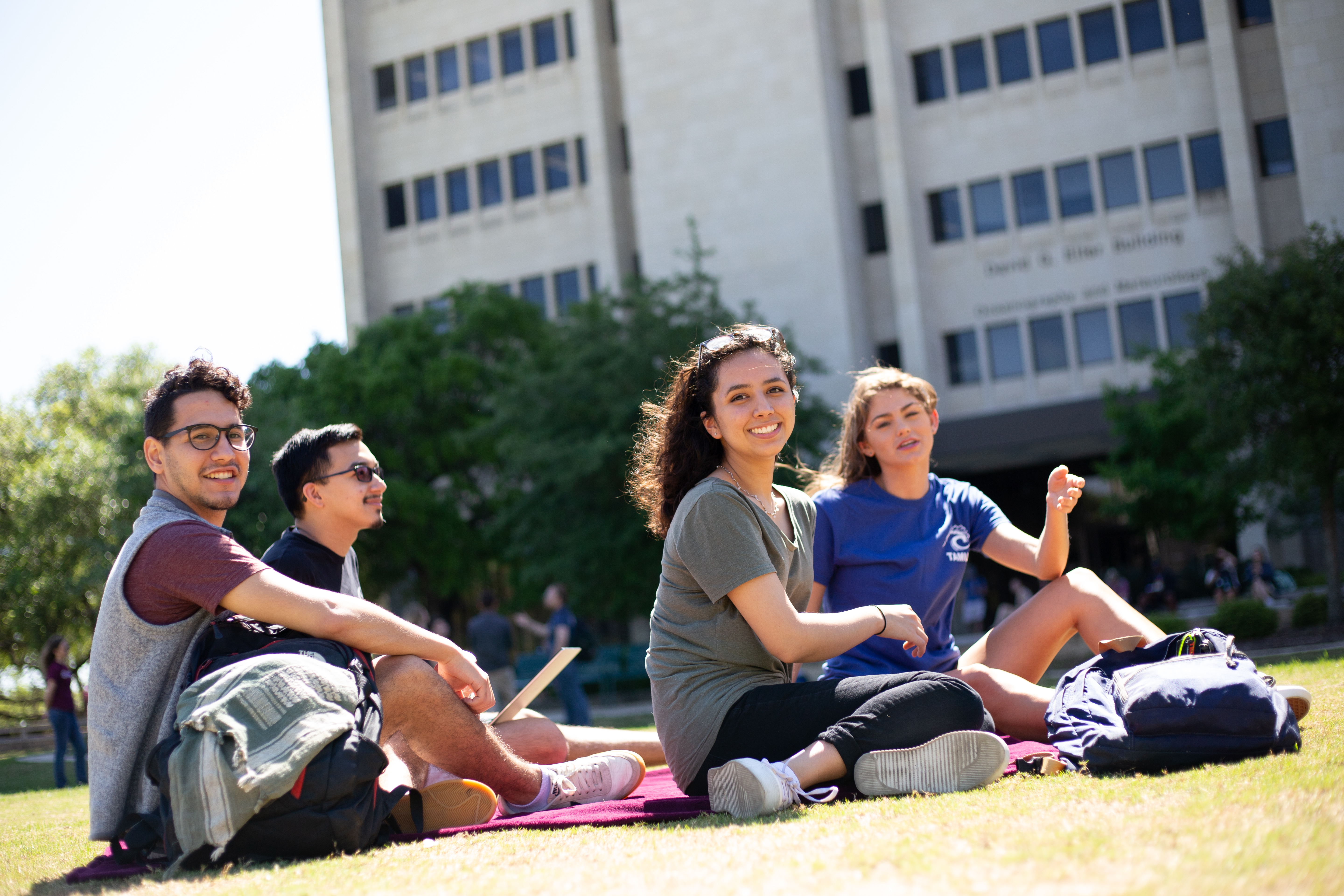 students sitting on campus near a building