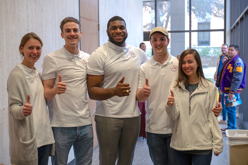 five students in white shirts with a thumbs up